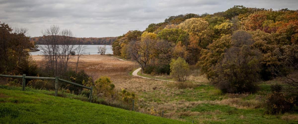 View of pastures leading to a lake. The trees are changing colors.