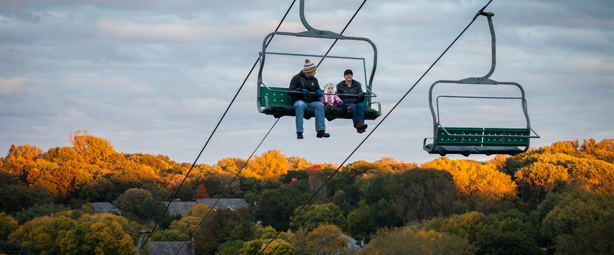 two people in a chairlift with fall colors behind them.