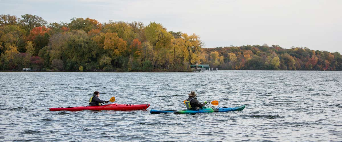 two kayakers paddling on a lake in the fall.