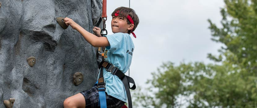 boy climbing on a rock climbing wall