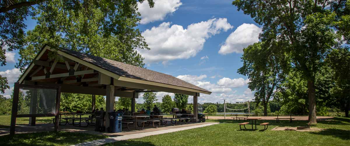 a covered picnic shelter near a sand volleyball court.