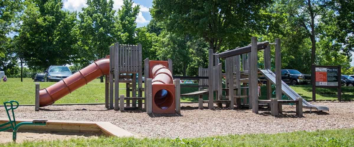 a wooden play area with red slides.