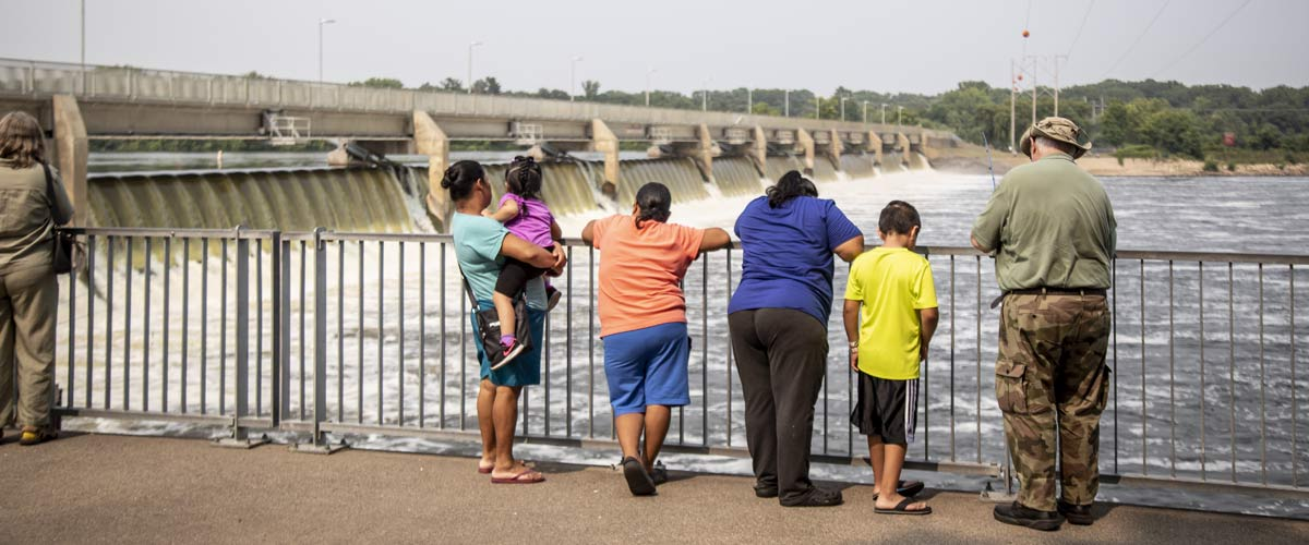 a family standing along a railing in front of the coon rapids dam.