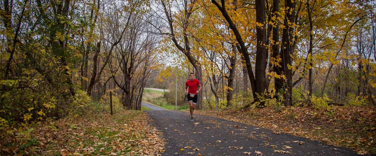 a runner on a paved trail in the fall.