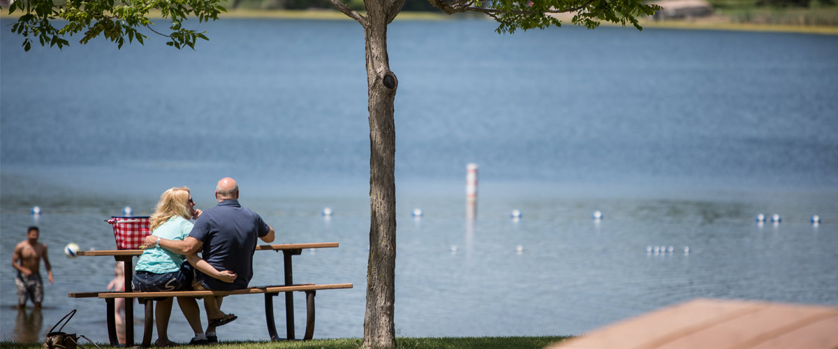 a couple has a picnic overlooking a lake.