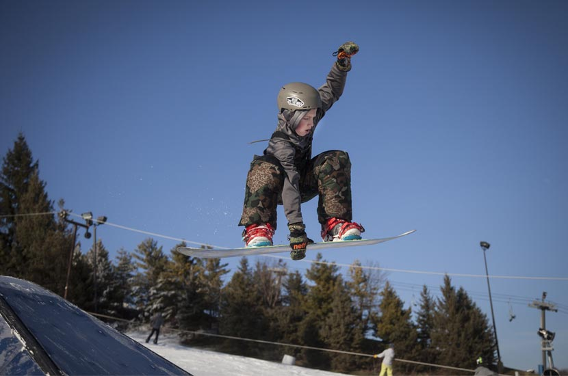 a snowboarder in the air with chairlifts in the background