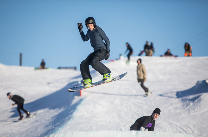 a snowboarder in the air off a jump. The hill and other snowboarders are behind him.