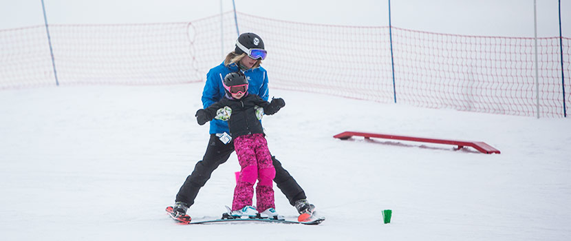 an instructor helping a young child learn to ski