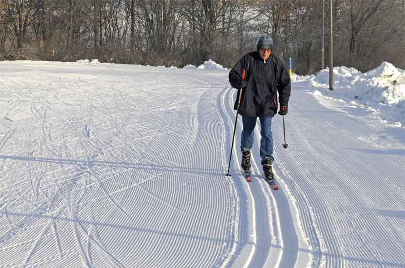 an older man doing classic cross-country skiing on a groomed trail.