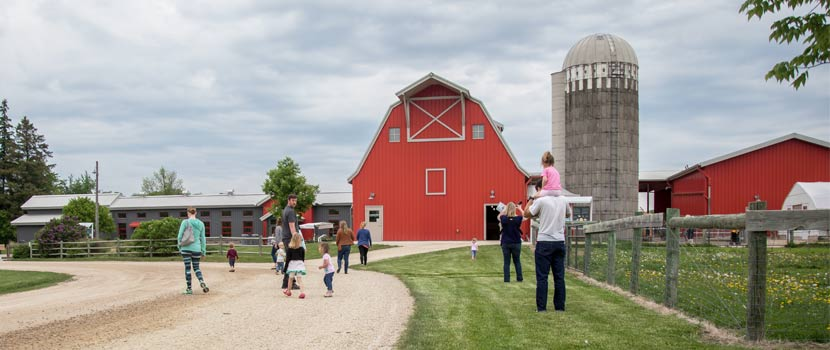 people walking up to a red barn