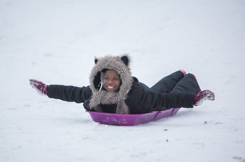 a girl in a black snowsuit rides a purple sled on her stomach. Her arms are stretched out like an airplane and she's smiling.