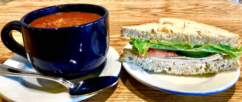 tomato soup in a large blue ceramic mug next to a sandwich with lettuce and tomato on grain bread.