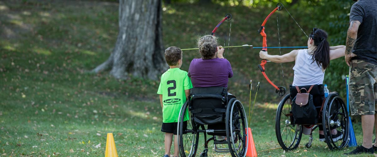 a woman shooting a bow and arrow from her wheelchair.