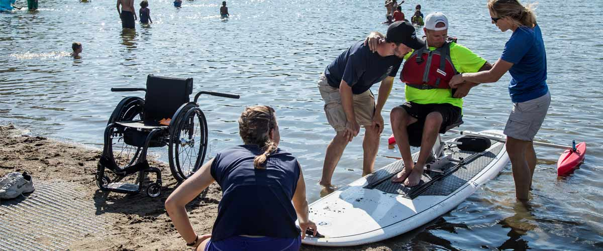 a man being helped from his wheelchair onto an adapted  paddleboard.