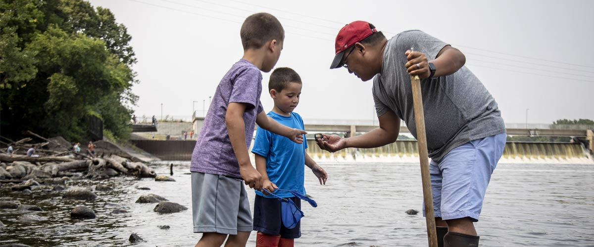 a dad shows his sons something he found while wading in the water.