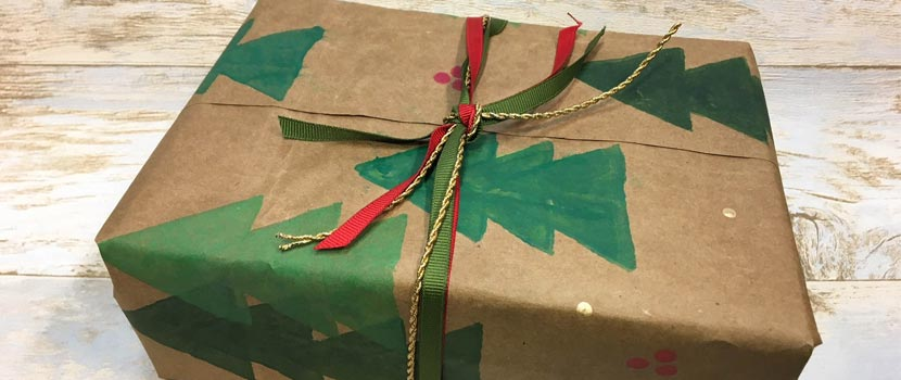 a gift wrapped in brown paper bag that's been decorated with stamps to have christmas trees and holly on it. REd, green and gold ribbon is tied around it in a bow.