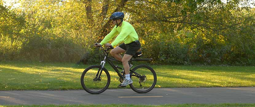 a man biking on a paved trail in the summer or fall.