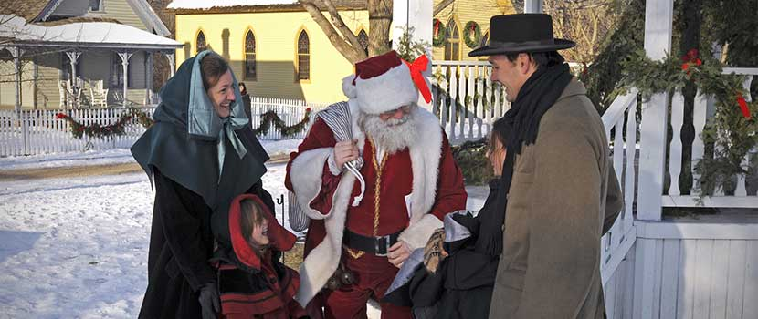 a man dressed as Santa Claus greeting a family 1800s costumed characters