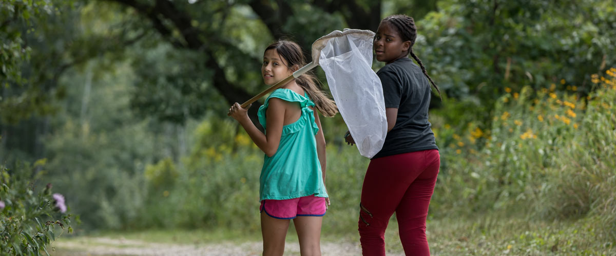 two girls walking down a trail looking back at the camera. One is holding a net.
