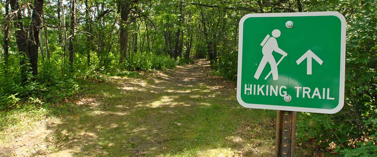 a sign that says hiking trail with a symbol of a hiker. A wooded path can be seen behind it.