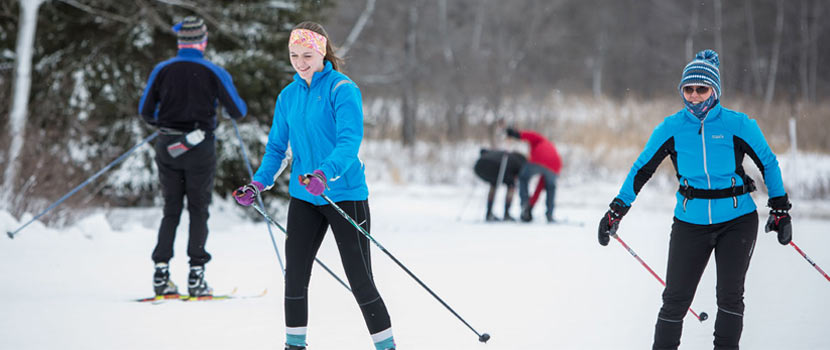 cross-country skiers smiling on the trail.