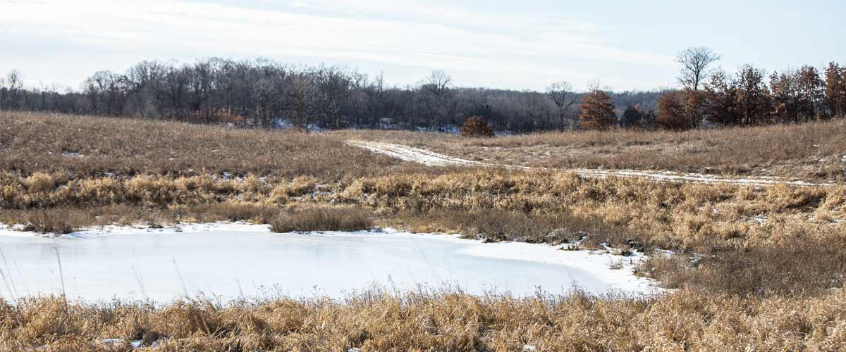 a frozen lake in a prairie with bits of snow on the ground.