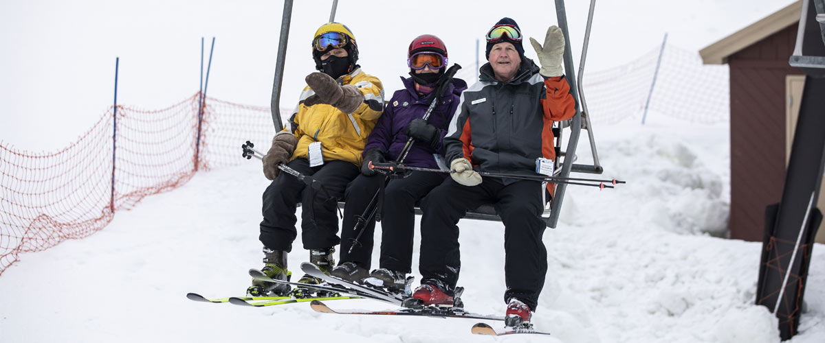 Three older people on a chairlift waiving at the camera.