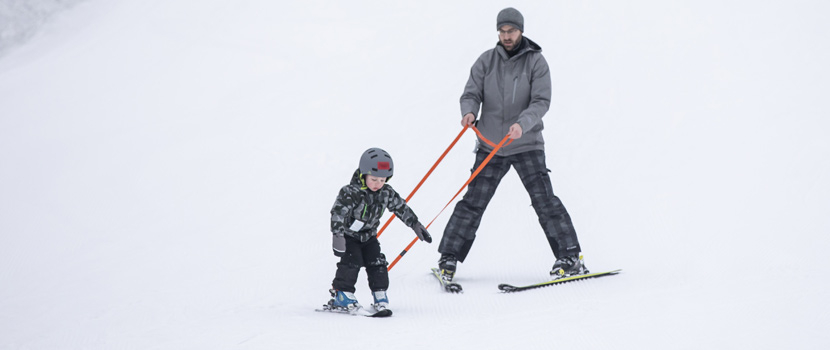 a man giving a child a downhill skiing lesson.