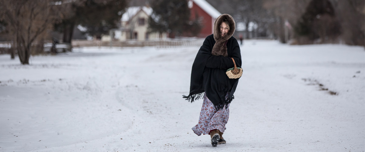 a woman in historic dress walking in the snow.