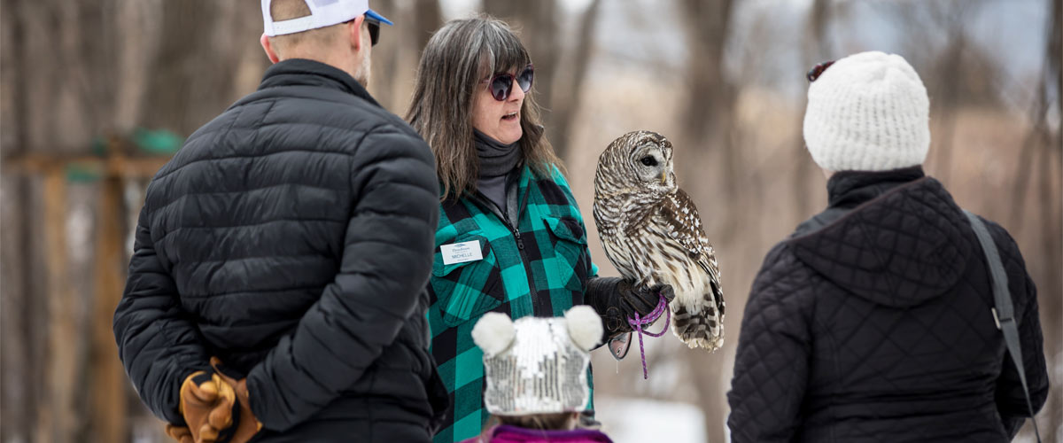 a woman holding a barred owl, with two adults and child watching.