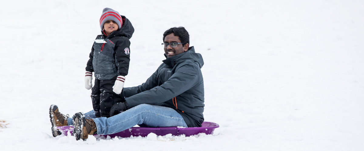 a dad and his son at the bottom of the sledding hill,