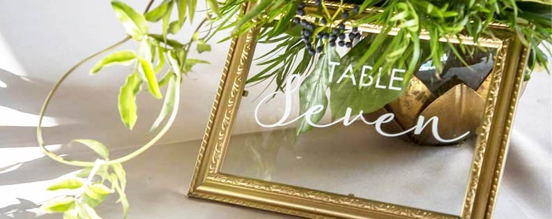 a gold frame with white lettering on the glass that says table seven. It's tucked under a plant.