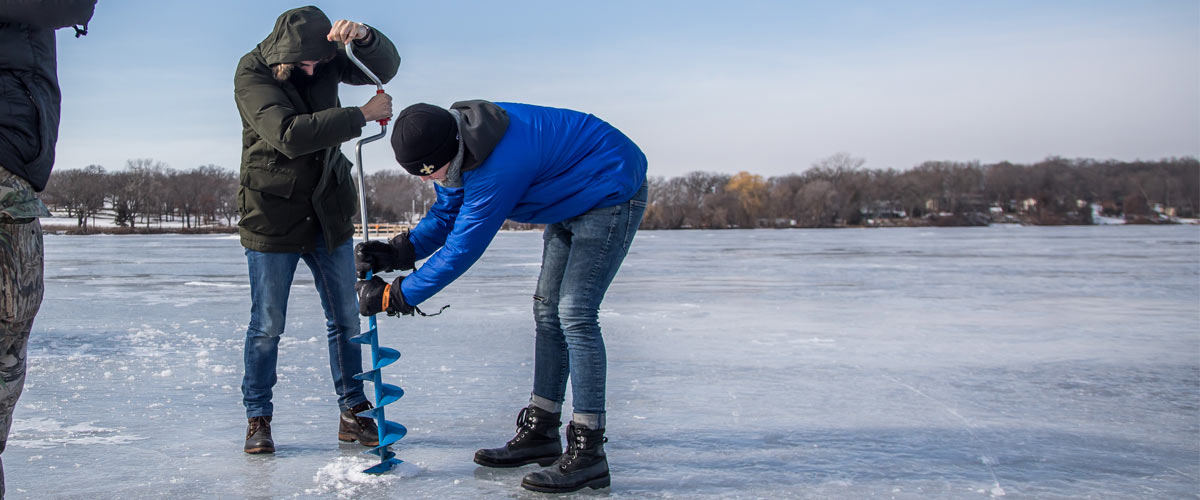 two people drilling a hole in the ice on a lake.