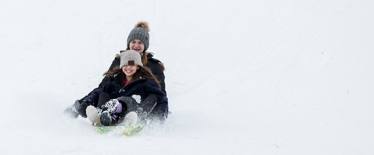 a teenage girl and a younger girl fly down a hill on a plastic sled