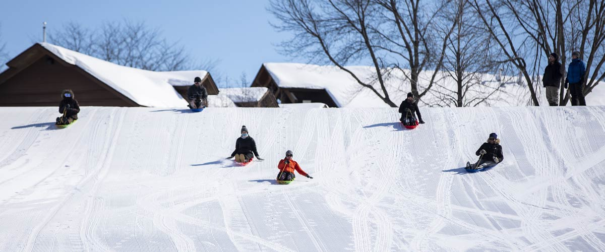 Six adults sledding down a big hill. A lodge is visible in the background.
