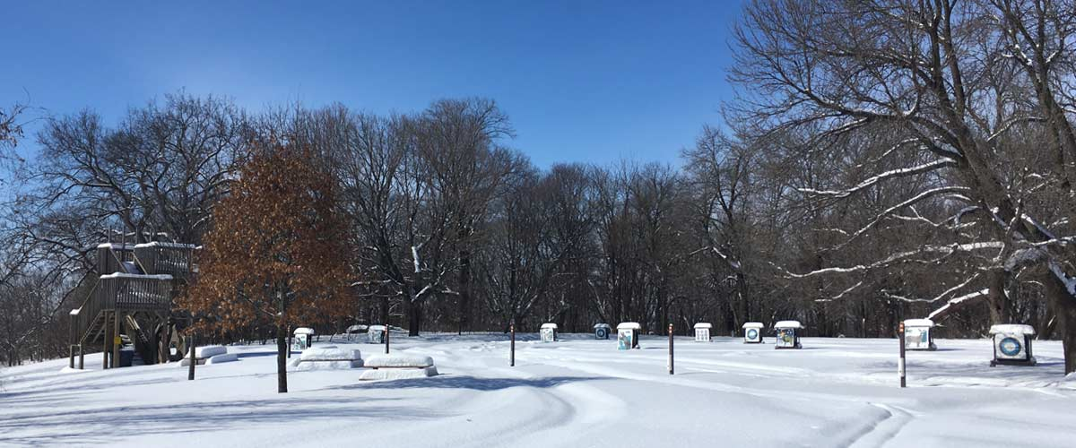 an archery range in the winter on a sunny day.