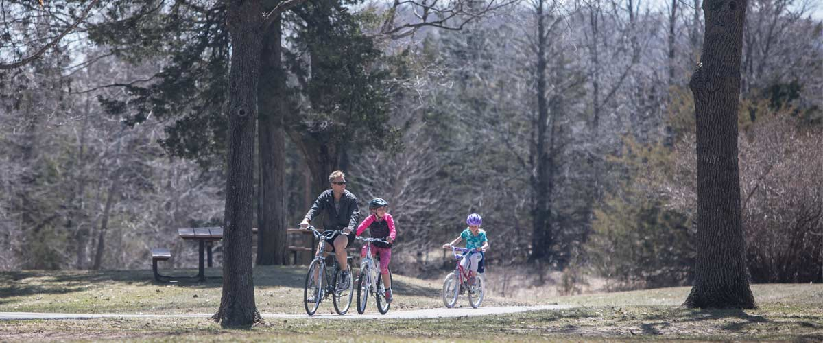 a man and two children biking through an open area with some trees.
