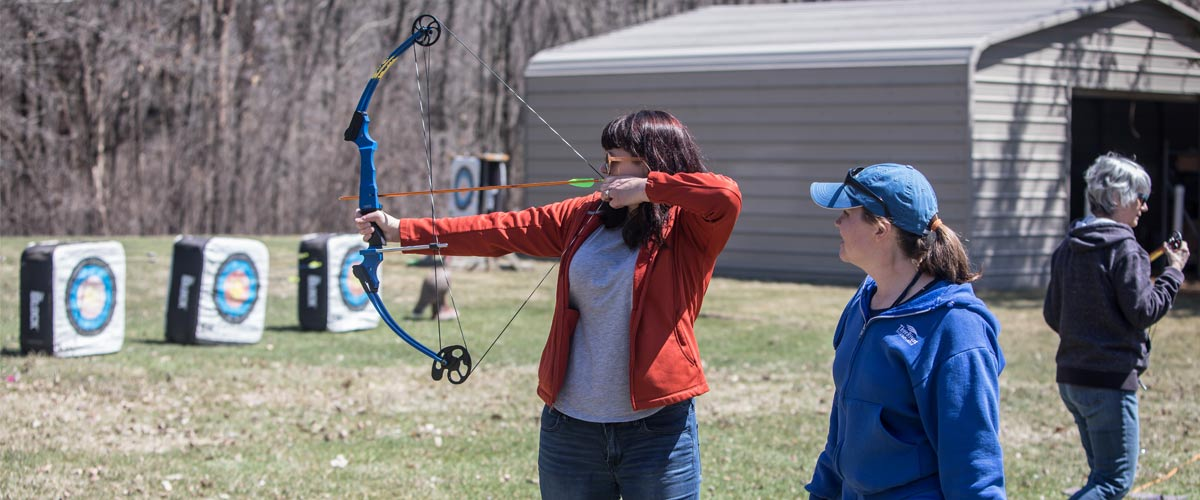 a woman aims her bow at targets while another woman instructs her.