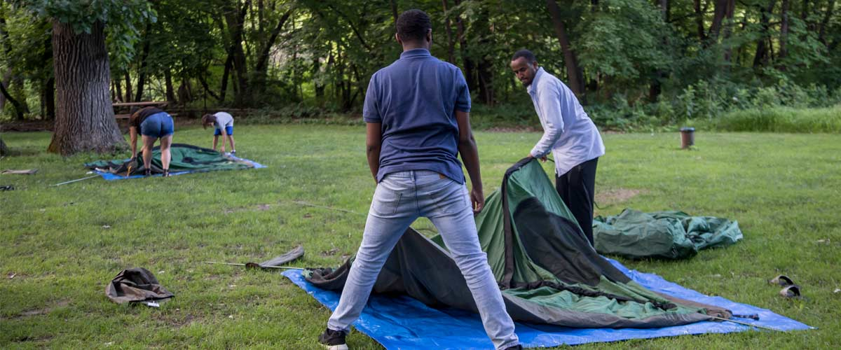 two men work together to set up a green tent.