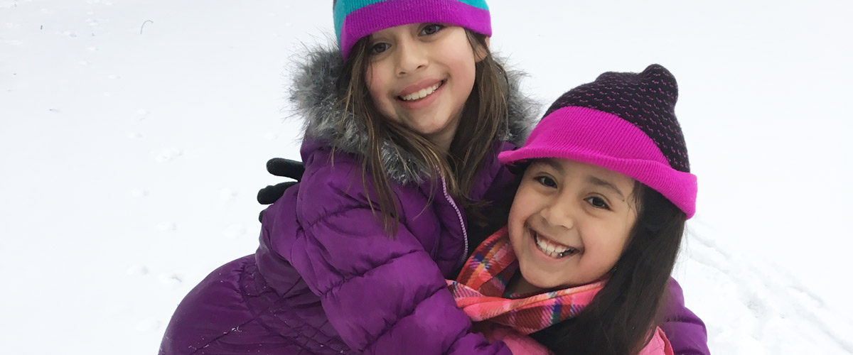 two girls smiling on a snowy day.