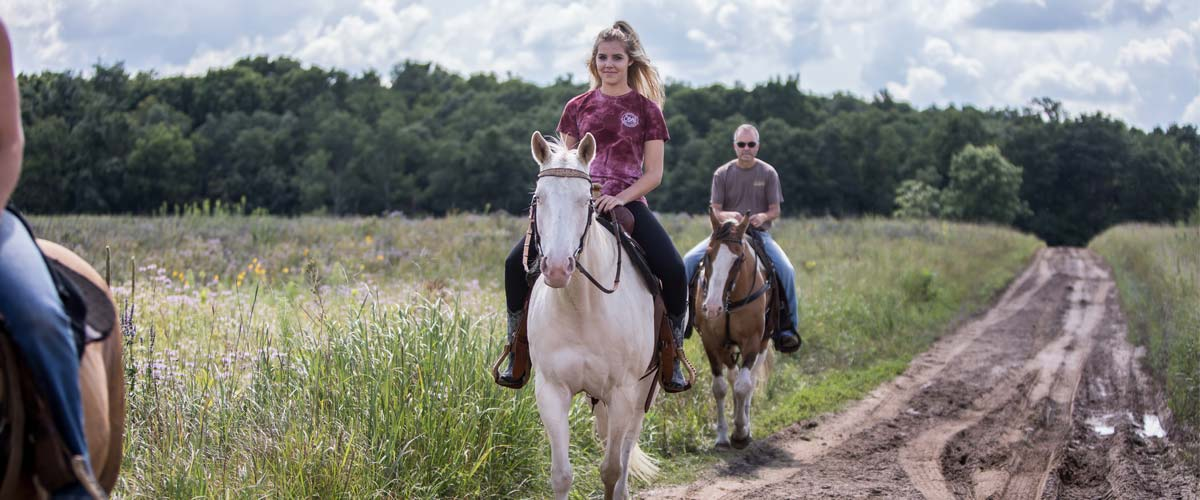 A woman on a white horse and a man on a brown horse coming down a trail through a prairie.