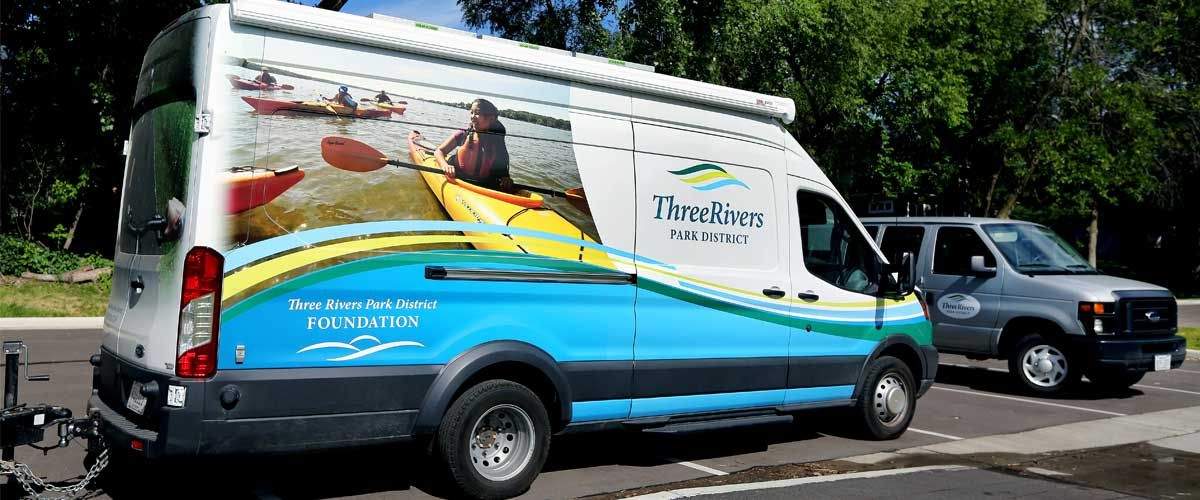 A van with the three rivers logo and an image of people kayaking on the side.