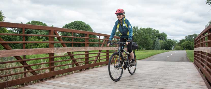 a woman in a blue jacket and red helmet smiles as she bikes over a wooden bridge.