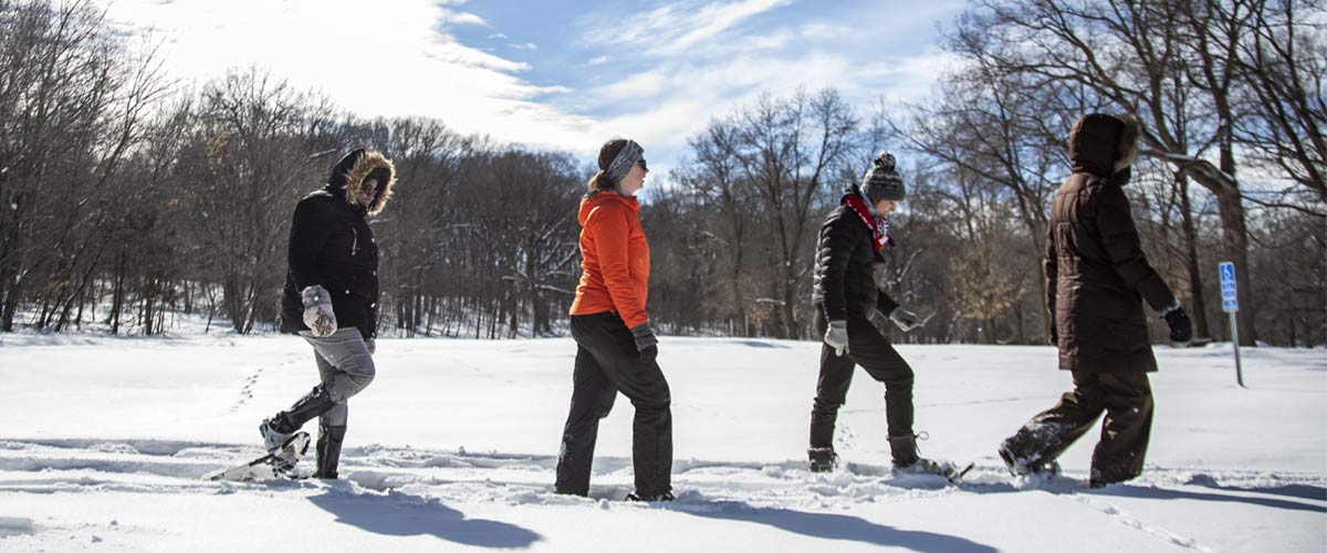 four people snowshoeing through a snowy park