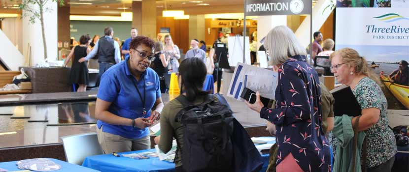 a three rivers employee talks to people at a health fair.