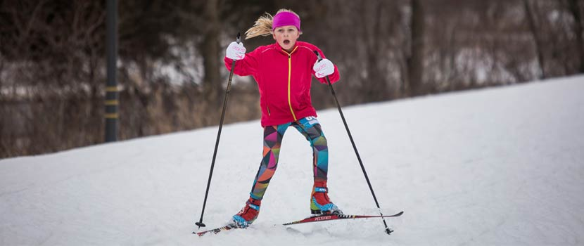 a blonde girl in a pink coat cross-country skiing.