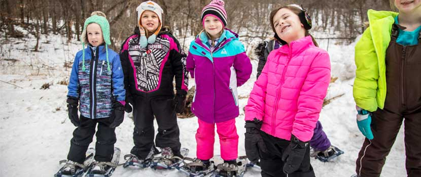 a group of young girls in colorful coats with snowshoes on.