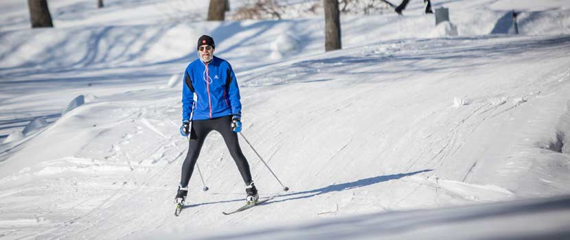 a man in a blue jacket cross-country skiing down a small hill.