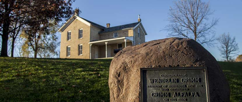 a yellow brick farmhouse with a memorial boulder in front of it.
