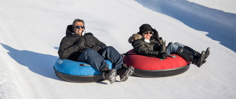 Two people on blue and red tubes going down a tubing hill.